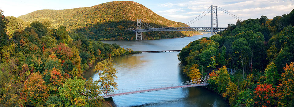 three bridges spanning over a large river in the Fall
